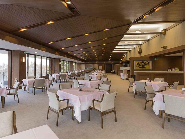 画像: ロビーと同じくコース側に天井が傾斜している、明るいレストラン。20卓