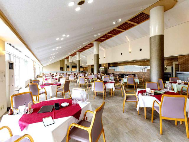 画像: 大きな空間がゆったりとしたくつろぎ感を醸し出すレストラン。窓からはコースが見える。15卓