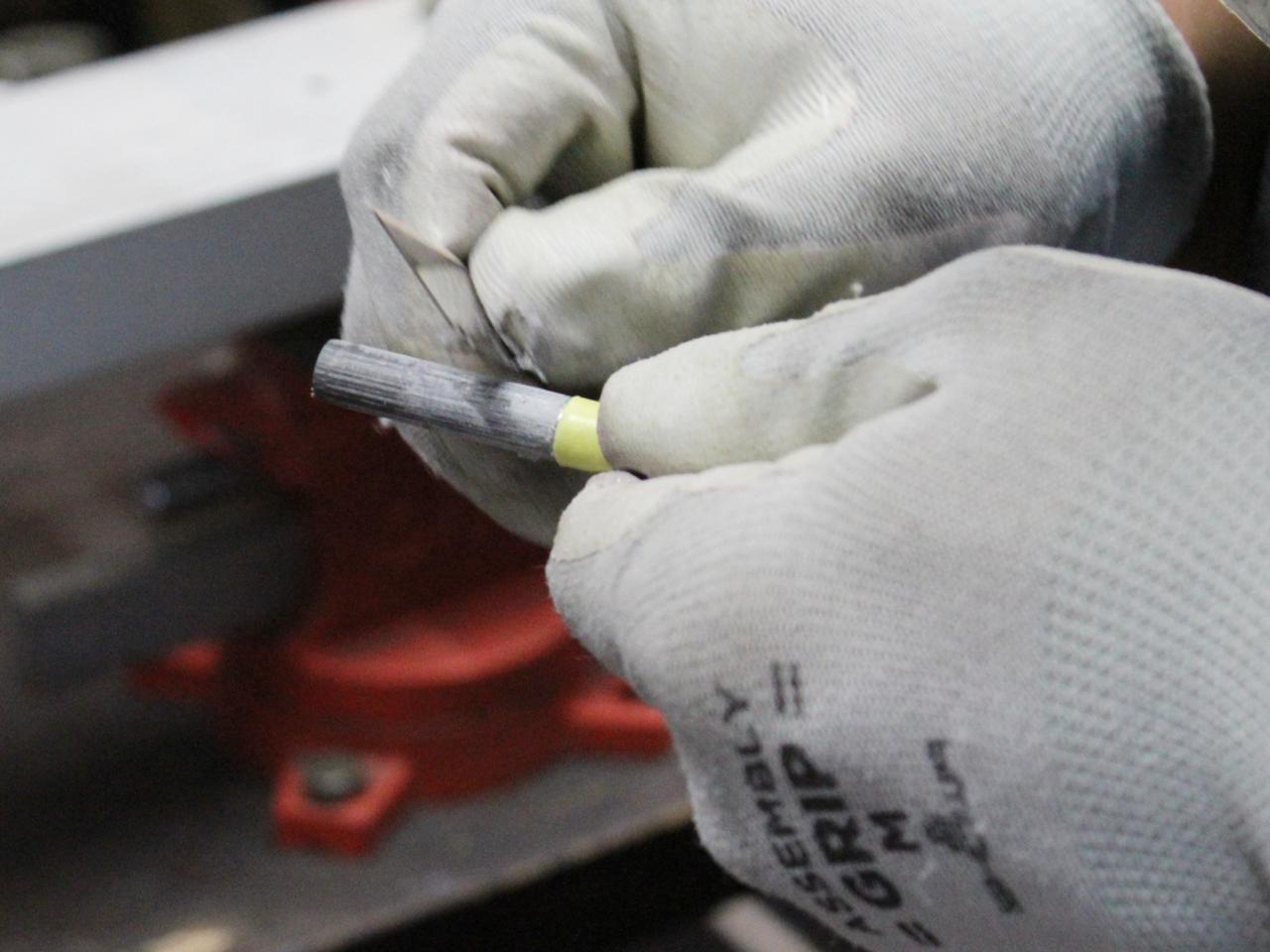 画像: ヘッドと接着するために、カッターの背を使いシャフト先端の表面の塗装だけを削り取っていく