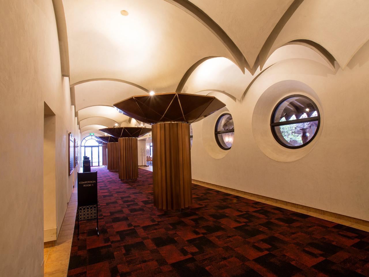 画像: ロビーから続く通路。左はコンペルームが並び、右奥にレストラン出入口がある