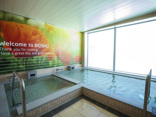 画像: 女性浴室。湯船が2槽あり、ポピーの花のプリント写真が貼られている
