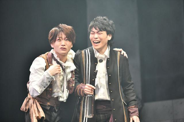 画像: ヴラドの計画により商売が上手くいく布商人 ティボル:新井裕士(左)とミハイ:後藤菊之介(右)