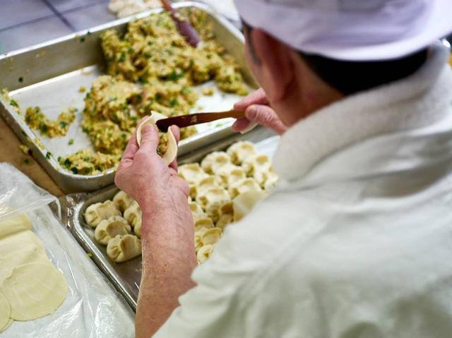 画像: 熟練の職人による仕込み。野菜多めの餡を厚めの皮に包んでいく