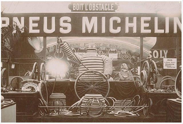 画像: 今の愛らしいキャラクターとは異なり、初期のビバンダムはこんな感じ。葉巻を吸ったりビールを飲んだり・・・とやり放題。 Stand-Michelin-au-Salon-du-Cycle-de-1898_history (c)Michelin