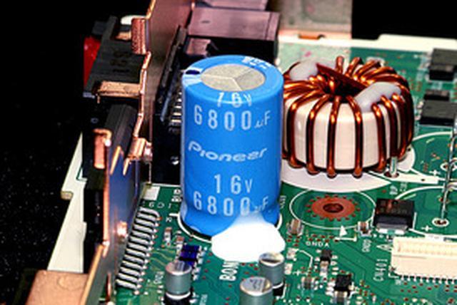 画像: オーディオ電源回路には、フルカスタムアルミ電解コンデンサーや高音質トロイダルコイルを採用。コンデンサーは、電解液の調合はもちろん、制振性能を高めた専用スリーブ(表面の青いカバー)までカスタマイズしている。コイルは線径を太く、コアの高さを上げるなど低抵抗化を実施している。これにより低音のグリップ感や制動力がアップしているという。