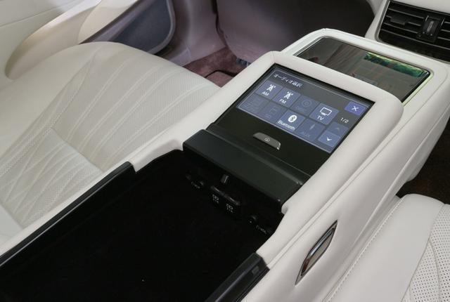 画像: リアシートバックの中央を倒すと、リア用のコントロールパネルディスプレイがあらわれる。オーディオ操作のほか、エアコン操作なども行うことができる。