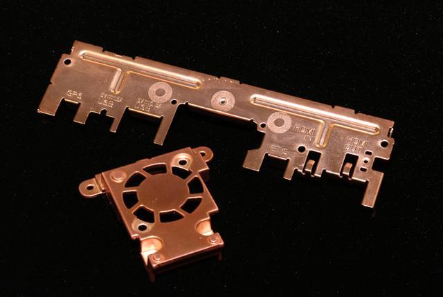 画像: 銅メッキパーツ同士が接する箇所ながら、ノイズコントロールの観点から絶縁すべき部分も存在する。その一例がリアパネルとヒートシンクの接点、画像のようにリアパネル側のビス穴部分に絶縁シートが挟み込まれている。