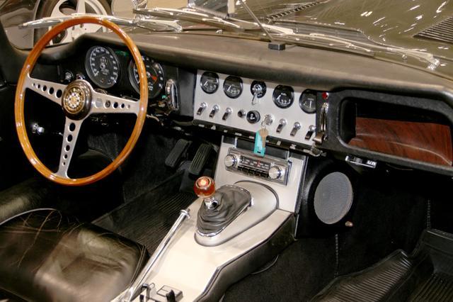 画像: Eタイプのコンソールには、シンメトリカルなデザインのラジオがマウントされていた。また、センターコンソールの両サイドにスピーカーが配置されるという、ユニークなレイアウトが印象的だった。