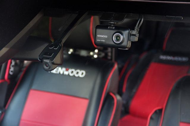 画像: デモ用にフロントガラスへ取り付けられた2つのドライブレコーダーとカメラ。左はレコーダーとカメラが分離している彩速ナビ連携型のDRV-MN940、コンパクトなため、視界の邪魔になりにくく軽量で装着もしやすい。右は単独型で定評があるDRV-MR740のフロントカメラだ。