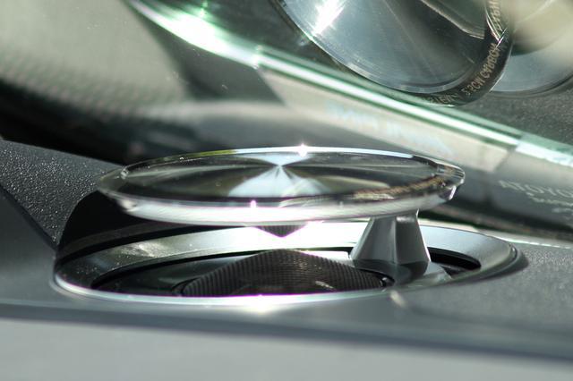 画像: リフトアップスピーカーには画像奥の支柱で支えられたアクティブトップカバーが、グラファイトダイアフラムの前面を覆うように設計されている。アクティブトップカバーには円錐型の音響プレートが下向きに形成されていて、音場効果を高めるよう企図されている。