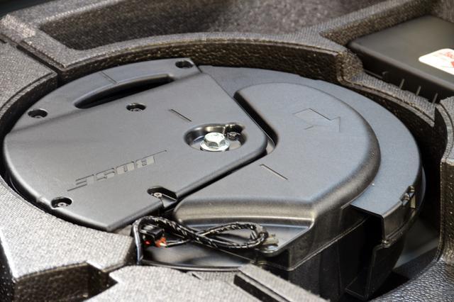 画像: サブウーファーを車室内側から見ると、低音を送出するポートが確認できる。トップパネルにはBOSEのロゴと、ユニットの固定向きを示す矢印が見える。