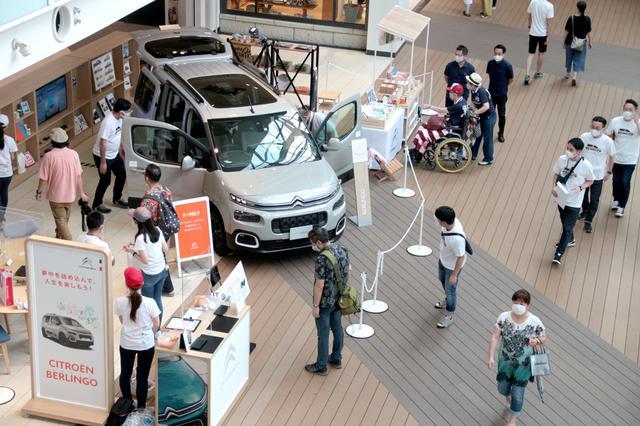 画像: ららぽーと豊洲のセンターエントランスに設けられた展示ブース。車両横にはノベルティ販売ワゴンも置かれている。