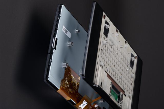 画像: 新旧ディスプレイ部を比較してみた。画像左は前作のディスプレイ部で背面パネルが取り除かれたもの、右がCN-F1X10BLDだ。圧倒的な薄型設計が実現されていることがわかる。(Photo:Atsuko Goto)