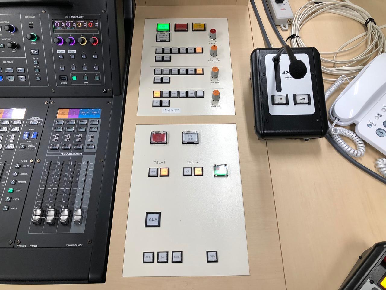 画像: 「M-5000」が埋め込まれた特注デスクは、回線やモニターの切り替えボタンなどを搭載。これによって機材慣れしていない人でも簡単に操作できるようになっている