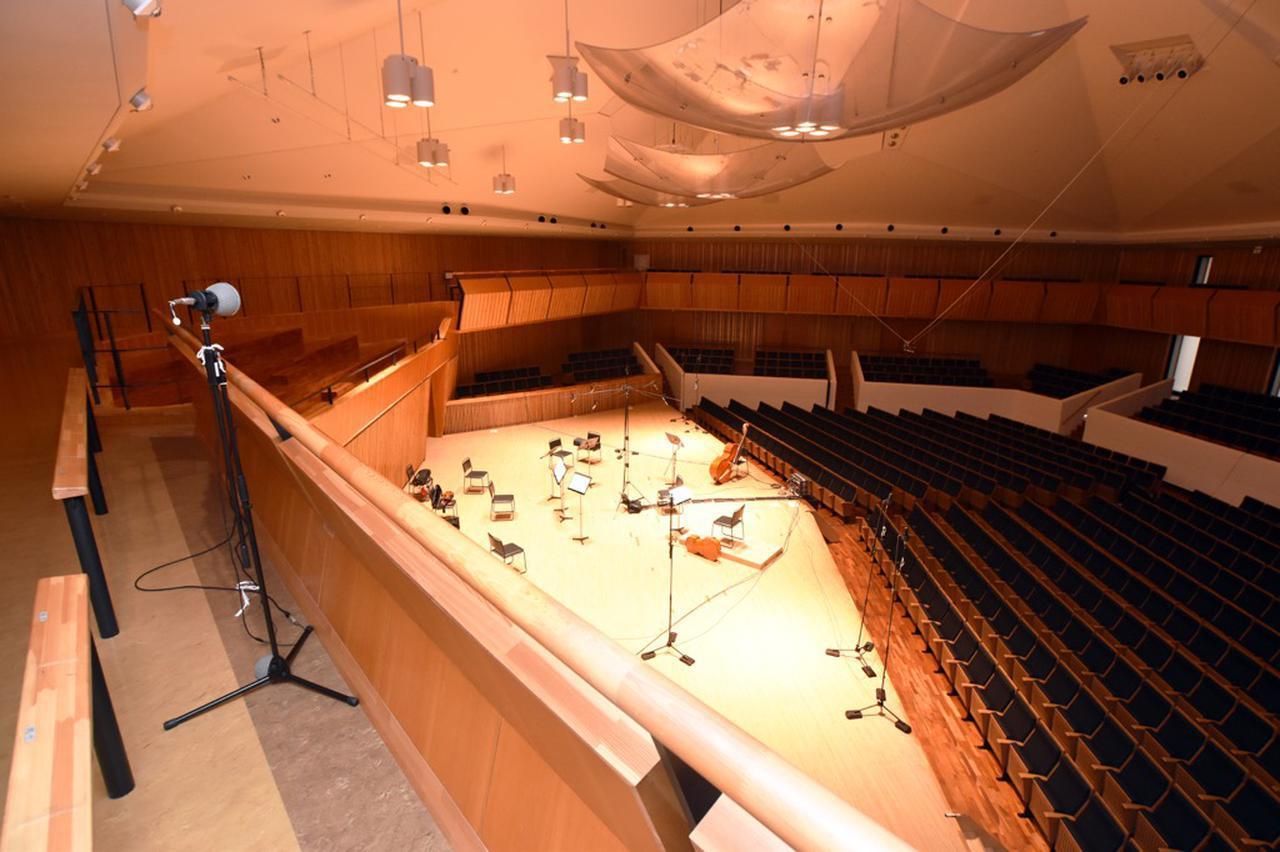 画像: サラウンドの録音にも向いていると沢口氏が語る五角形の大賀ホール。2階バルコニー席にセットされているのはハイトチャンネル用のマイク。こちらは2019年1月に行われた『ViVa Four Seasons』のレコーディング風景