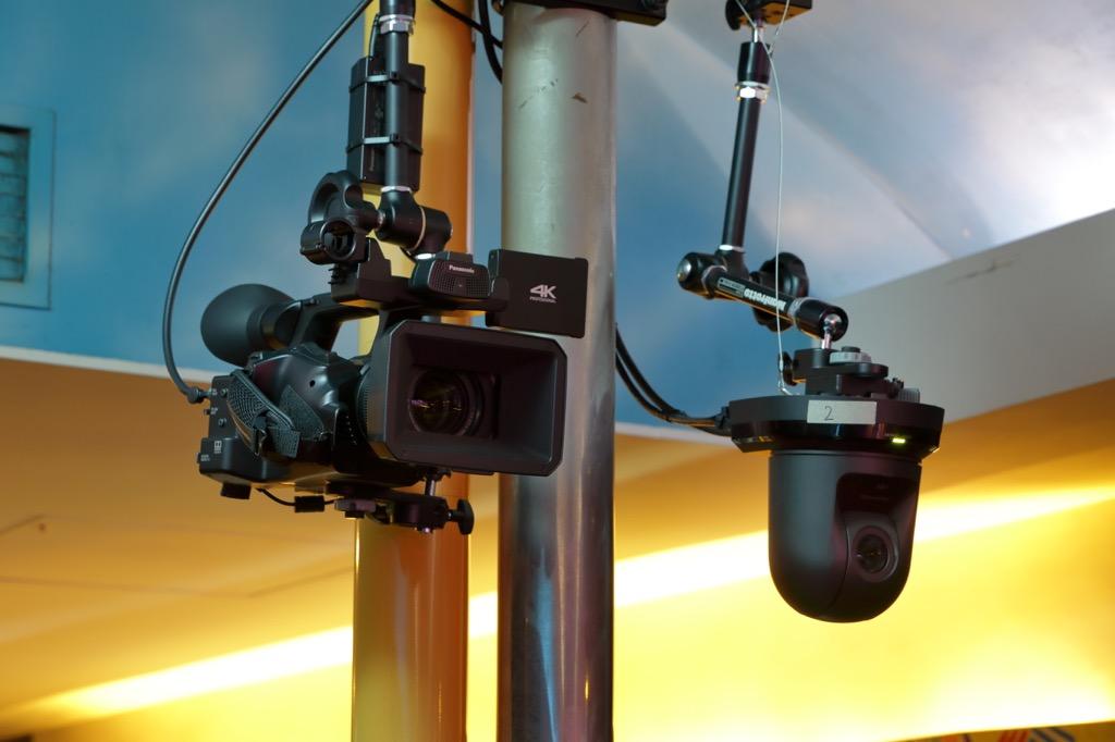 画像: ステージ正面の天井に設置されたメイン・カメラは、パナソニック AG-CX350(写真左)と同 AW-UE70(写真右)。どちらも4K対応で、AW-UE70はリモート・コントロールにも対応。V-600UHDからもコントロールすることができる(Ver.2.00以降)
