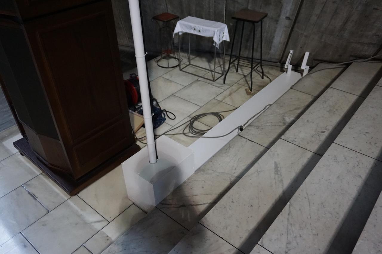 画像: 床が大理石でアンカーが打てないため、スタンドを特注し、壁にアンカーを打つことで固定された