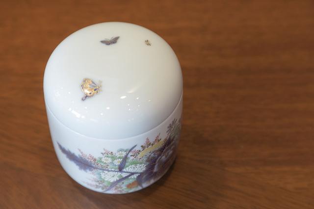 画像: 筒型の手元供養骨壷。側面の花の上を蝶が飛んでいるように見える、立体的な絵が魅力的。