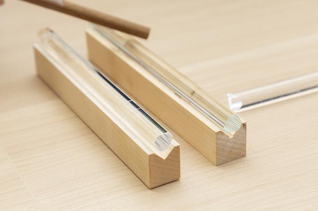 画像: ガラスの素材となる成分の配合を変えて作られた、2つの水平鈴の音を比べてみる。 手前の、透明度が高いガラスの方が余韻のある音が鳴る