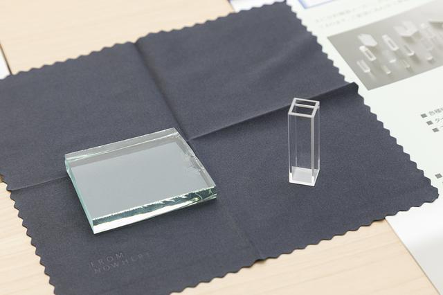 画像: 左側が窓ガラスに使用されるガラス。 右側の角柱状のものが、光学ガラスでつくられた検査容器