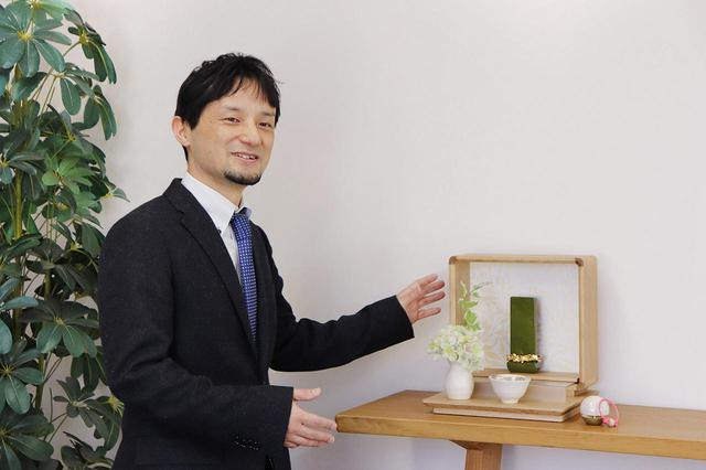 画像: 株式会社八木研 企画室課長 松木宏行さん。今期新作のオープンタイプ仏壇「ウィロー」と組紐リン棒の「くみわ」と共に