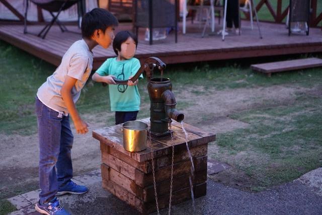 画像: 筆者撮影:井戸で水汲み。普段見かけない井戸に興味津々