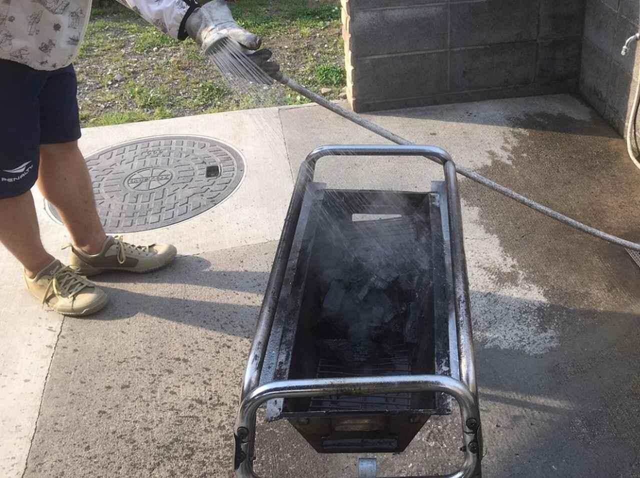 画像: 筆者撮影 ※逃げ腰で炭の黒汁を避けるオカダ タロウ。結構な距離まで水しぶきが飛んでくるので一苦労