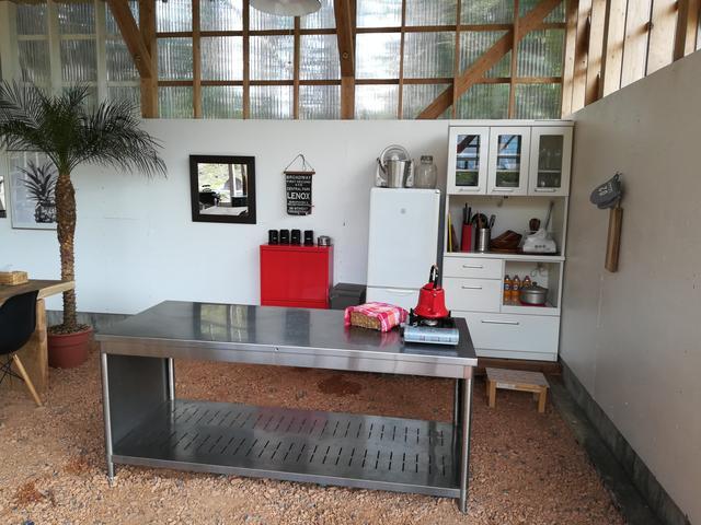 画像: 筆者撮影(貸切小屋の中の調理スペース。食器、冷蔵庫、ゴミ箱、カセットコンロなど豊富な無料レンタル品)