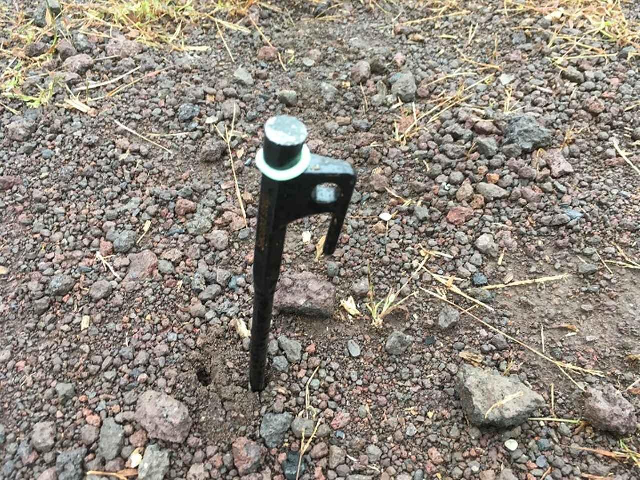画像: 筆者撮影:溶岩質の固い地面に刺さる鍛造ペグ