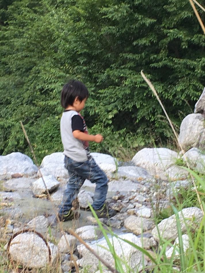 画像: 筆者撮影 川辺で自然素材を探す息子の様子