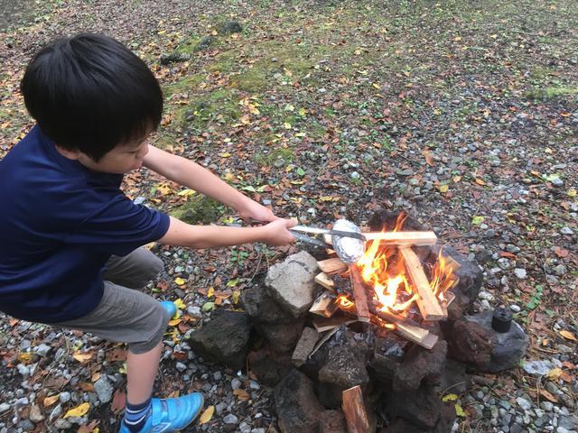 画像: 筆者撮影 アルミホイルで包んだりんごを焚火の中へ(怖がりながらも果敢に挑戦)