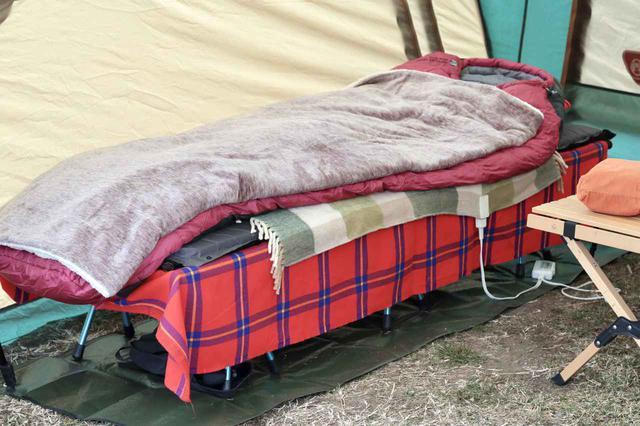 画像: 編集部撮影 寝袋の下に敷いているグリーンのチェックの布が電気毛布