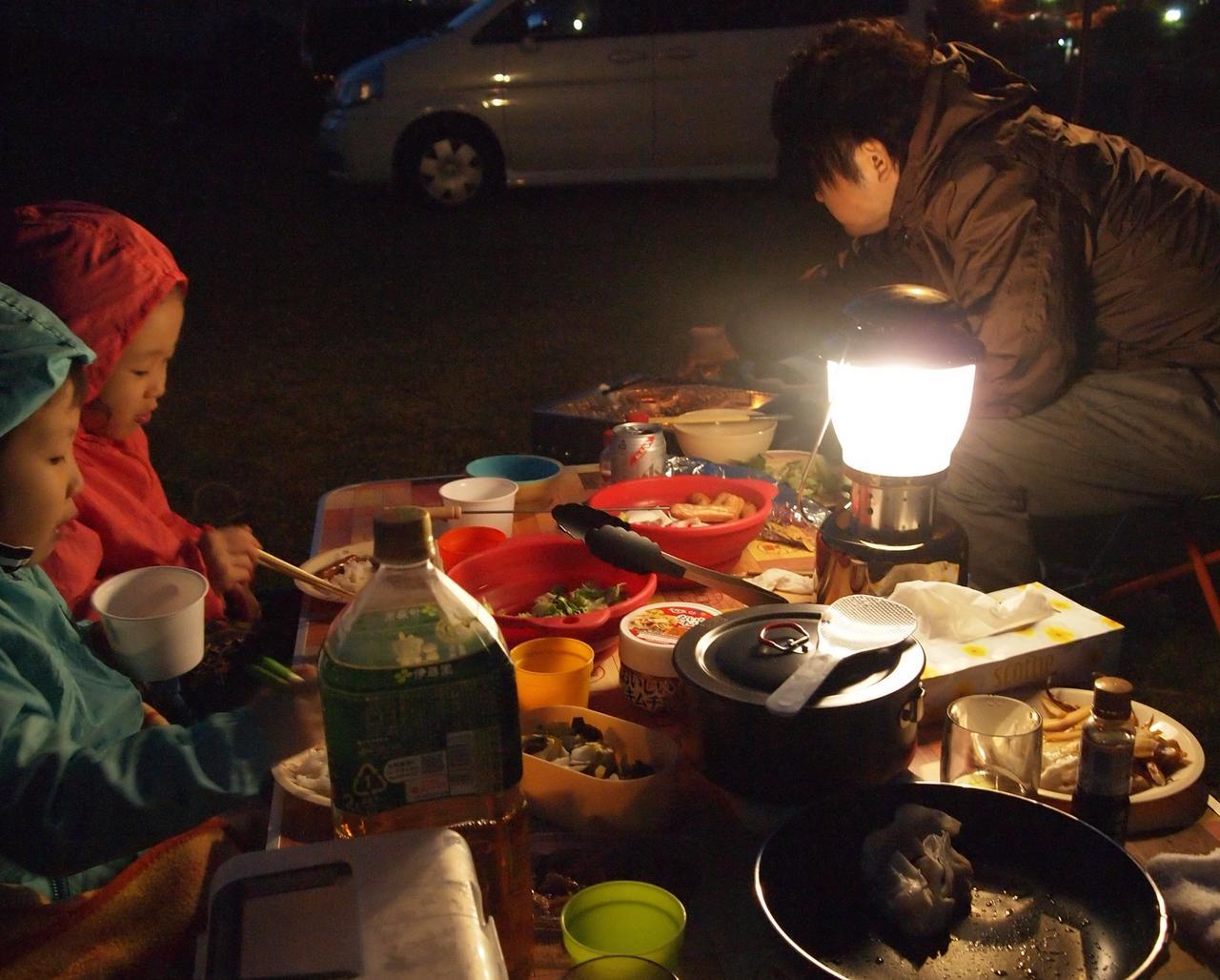 画像: 気温13度程度:膝掛けとホッカイロで暖をとり、何とかご飯を食べている子ども達。