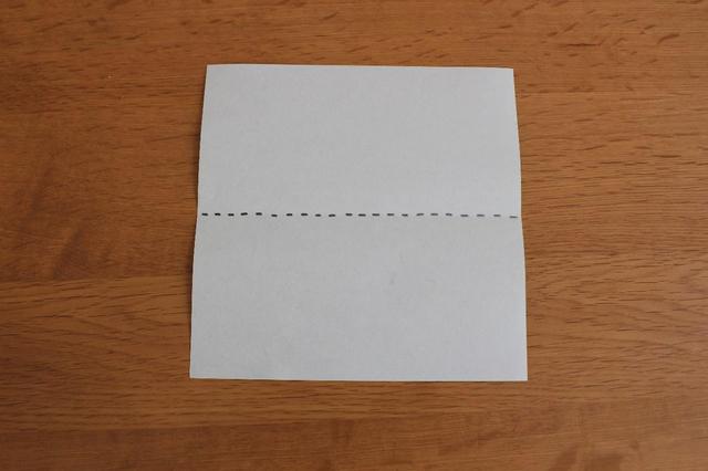 画像: 1.裏側をテーブルに置いて点線で上から半分に折る (筆者撮影)