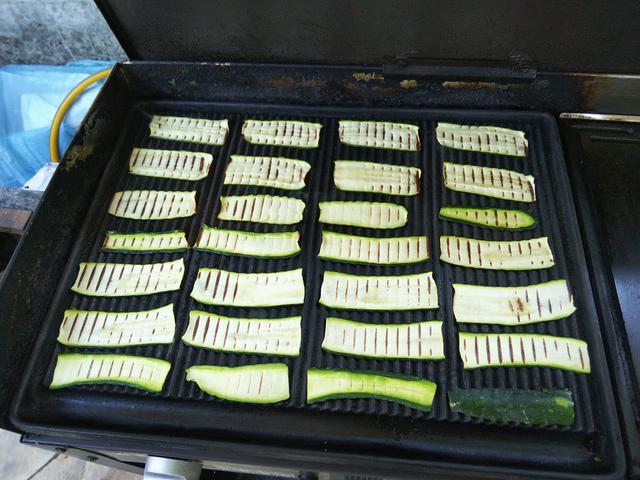 画像: BBQ用の鉄板上に5㎜程度にスライスしたズッキーニを並べる (筆者撮影)