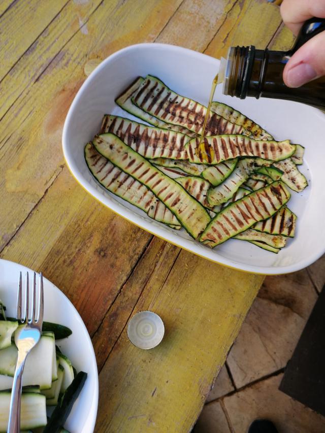 画像: 焼いて塩を振ったズッキーニにオリーブオイルをかける (筆者撮影)
