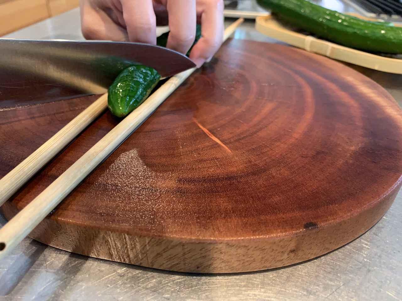画像: 筆者撮影(菜箸できゅうりを挟むことで、下まで切りすぎるのを防ぎます)