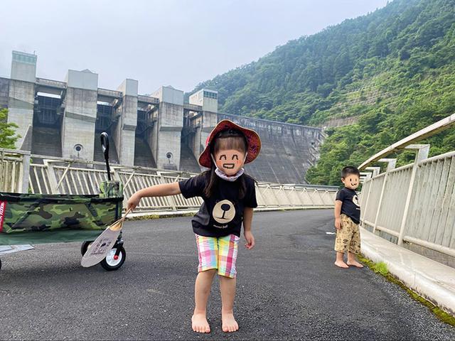 画像: 筆者撮影 日吉ダムをバックに満面の笑みの娘でした