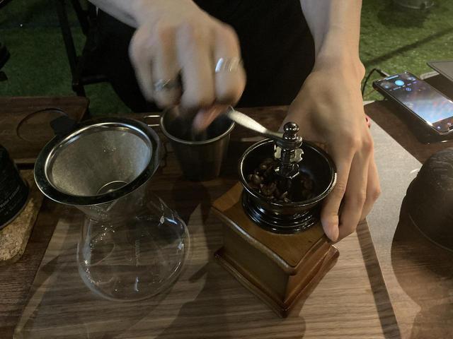 画像: 豆挽き初体験の筆者 (筆者撮影)
