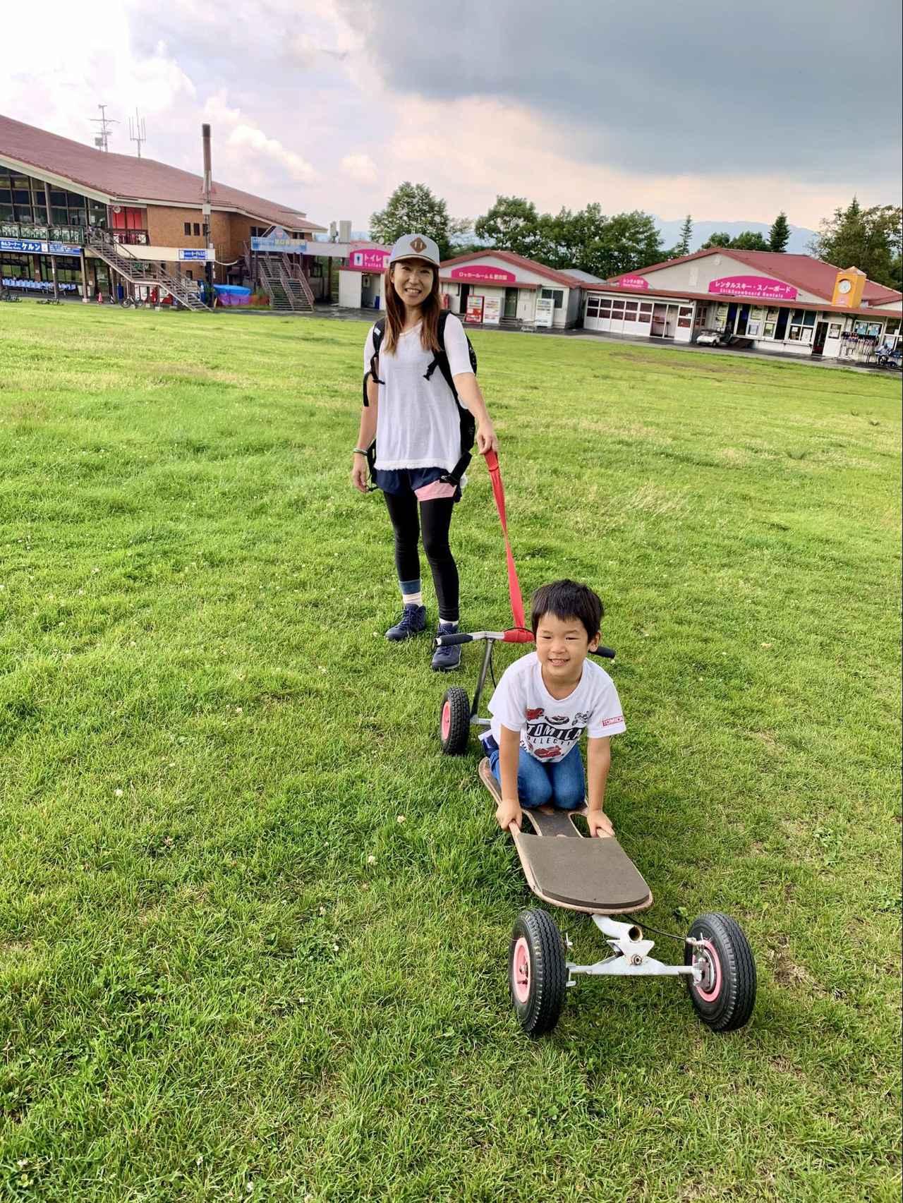 画像: (筆者撮影)ポッカールに乗る息子 通常はハンドルを持って芝生を滑走します