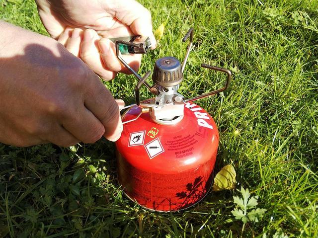 画像: ライターなどの火を近づけながらツマミを反時計に回して開栓 (筆者撮影)