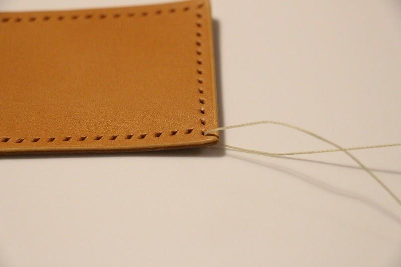 画像: 筆者撮影 1つ目の穴から出して糸を左右均等の長さにします