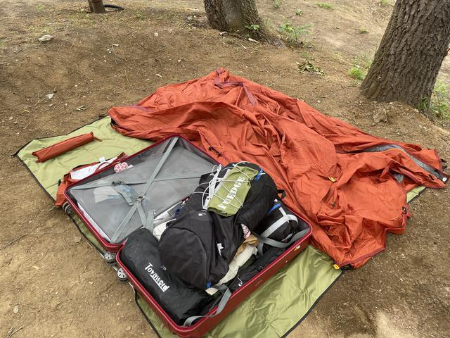 画像: 筆者撮影:グラウンドシートはファミキャンで使ってる手持ちの「ソロキャンプ用テントのサイズに対してはちょっと大きめなやつ」が、むしろ便利。余ったスペースが活用できるので、スーツケースを汚さないし、シートの上でキャンプマットの空気を入れたり寝袋を畳んだりもできる。