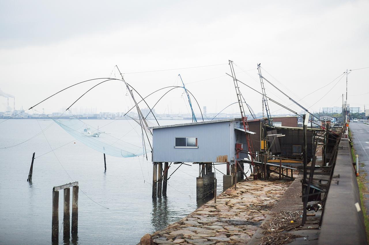 画像: 防潮堤から張り出した海上の小屋と、伸びる四つ手網。電灯で魚をおびき寄せる夜には、また独特の景観が生まれる