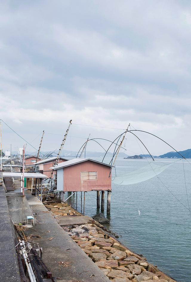 画像: 堤防に沿って並ぶ四つ手網。台風の影響などで20数棟に減ったが、最盛期は70棟ほどがあったという