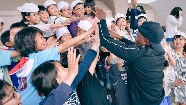 画像: 地元の小学生とハイタッチを交わすホターチョ・ムンジャーネ選手