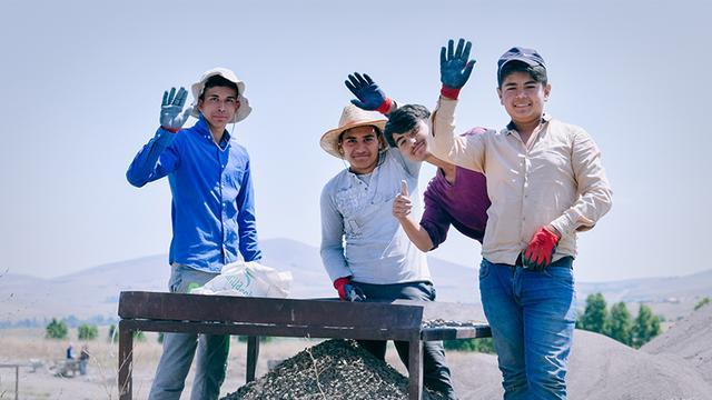 画像: 遺物をふるいにかける10代の作業スタッフ