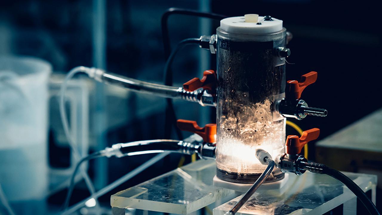 画像: 容器を外に出した形の装置。プラズマが光を放つ