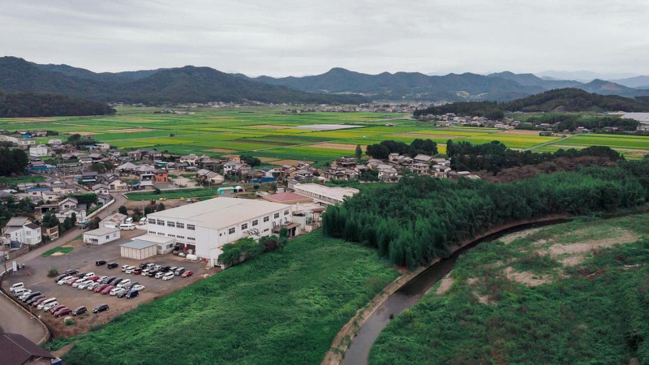 画像: 陽光園のすぐそばを旗川は流れる。左手前の白い建物が愛光園のクリーニング工場
