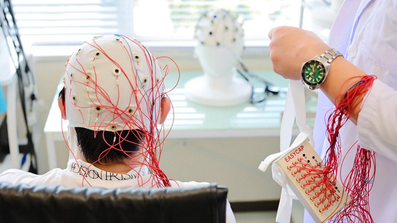 画像: 脳波キャップで、微弱な電気信号を頭皮で拾う